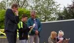 Raylano bekijkt samen met burgemeester Stapelkamp en directeur Arjen Smit de kalender, die alle kinderen krijgen ter herinnering aan het jubileum.