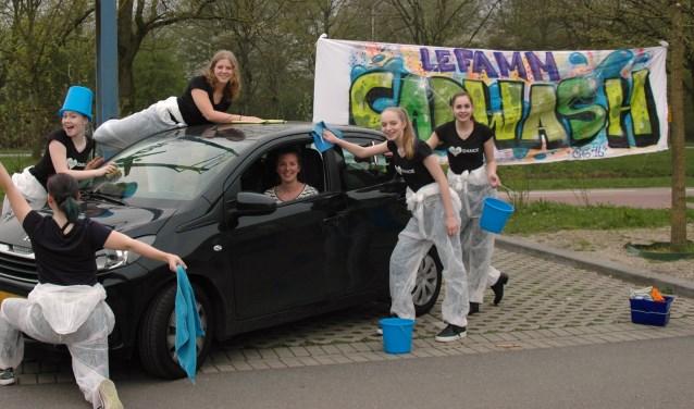 De leden van Lèfamm wassen de auto's met een dansje en een glimlach. Foto: PR