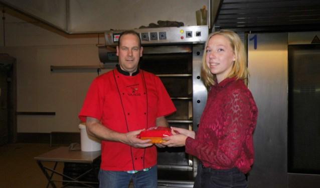 Femke Elferink overhandigt de cake aan bakker Gerard Vaags. Foto: Eva Schipper