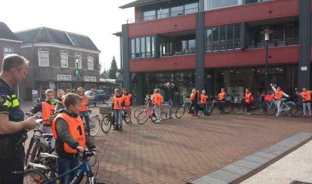 Onder toeziend oog van de Ruurlose wijkagent Tom Nijland gingen de leerlingen vanaf het Kerkplein van start voor het verkeersexamen. Foto: PR.