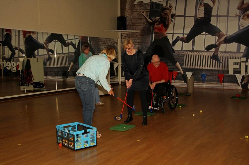 Burgemeester Besselink krijgt les in golf. Foto: Liesbeth Spaansen  © Achterhoek Nieuws b.v.