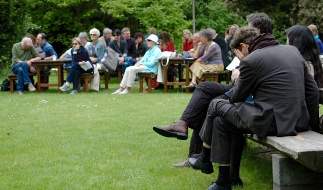Publiek luistert naar de voordracht van één van de honderd voorlezers. Op de voorgrond dichter Erik Lidner. Foto: Nadine Ancher