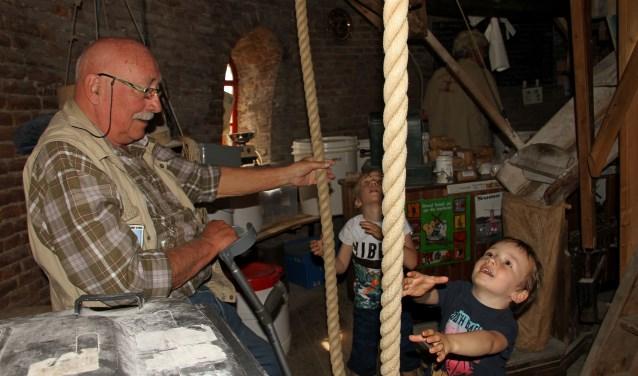 Molenaar Gerard Brugman laat kleinzoons Nik en Tim beleven hoe het luien gaat. Foto: Liesbeth Spaansen