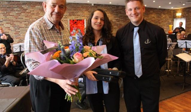 Bloemen als bedankje voor opa Bluiminck. Ook op de foto kleindochter Naomi en voorzitter Frank Spiekker. Foto: Nora Baks