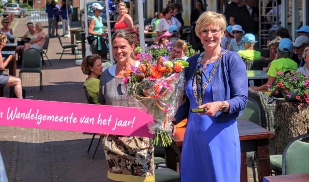 Burgemeester Marianne Besselink toont het beeldje dat hoort bij de titel Wandelgemeente van het jaar 2018. Foto: Luuk Stam