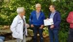 Jan Berendsen met de cheque die Fien Rouwhorst (links) hem in naam van haar man overhandigd  heeft. Midden: Harry te Molder. Foto: Alice Rouwhorst