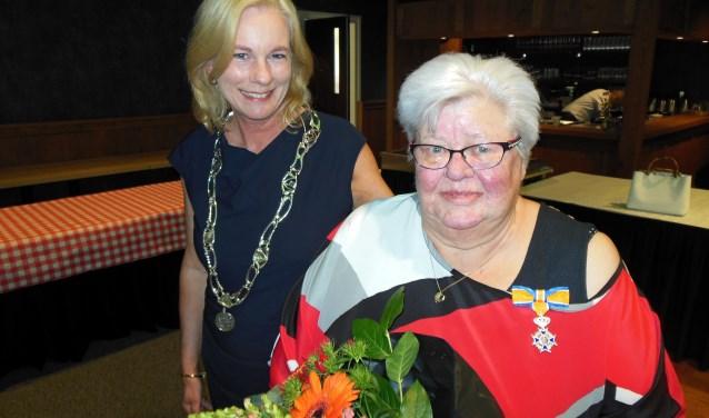 Geflankeerd door burgemeester Annemieke Vermeulen toont Cootje van der Meulen haar zojuist opgespelde Koninklijke Onderscheiding. Foto: Eric Klop