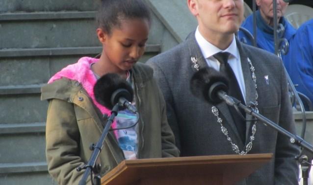 Suzie uit het asielzoekerscentrum leest een gedicht voor. Naast haar burgemeester Bengevoord. Foto: Bernhard Harfsterkamp