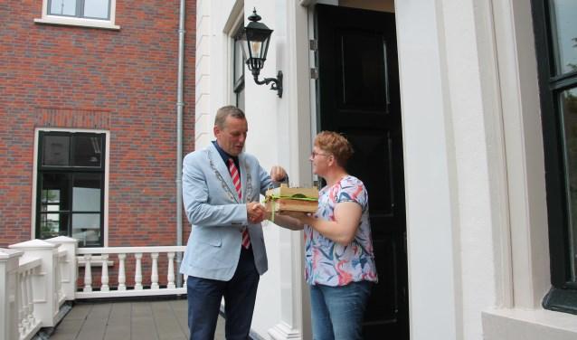 Burgemeester Stapelkamp neemt de kersen in ontvangst van Astrid Selman en laat ze zich goed smaken. Foto: Lydia ter Welle