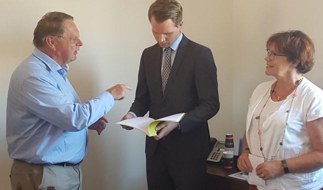 Jaap Cannegieter (l) biedt de petitie aan aan wethouder Bart Porskamp. Rechts Wilma van der Donk. Foto: Kyra Broshuis
