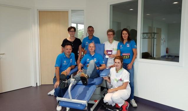De Roparunners proberen even een 'fiets' uit, die gekoppeld kan worden aan de stoel van de patiënt tijdens een behandeling met chemotherapie. Foto: PR
