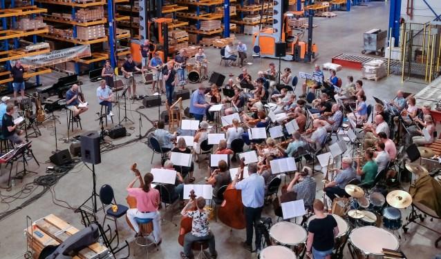 Ruim honderd muzikanten en zangers repeteren in het magazijn van Eurobolt. Foto: Burry van den Brink