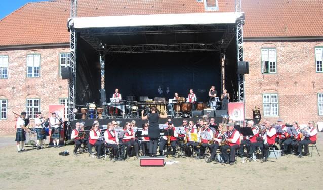 Muziekvereniging Volharding tijdens het optreden met een drietal leden van de Frederikshaven FDF Pipeband en Marc Ditters en Sandra Halfman. Foto: PR