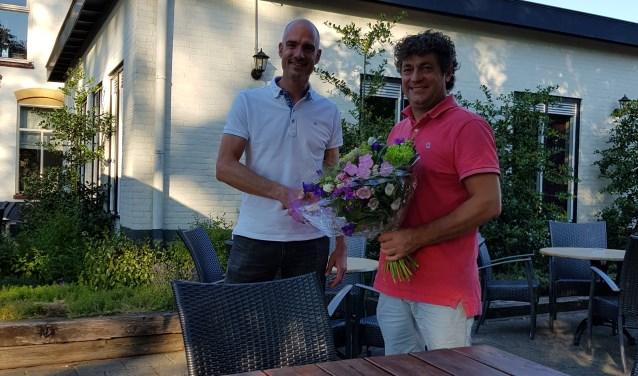 Hidde Bulten overhandigt het boeket bloemen aan Bert Ribbers. Foto: PR