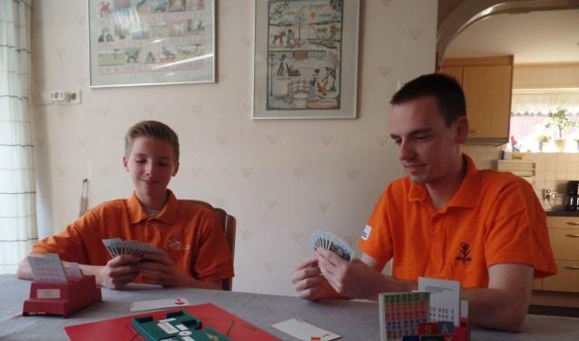 Kevin Gotink (rechts) en Jorn Essink doen aan de keukentafel van de familie Gotink uit de doeken dat je bridge speelt samen met een partner die tegenover je zit en tegen twee tegenstanders. Foto: Jan Hendriksen