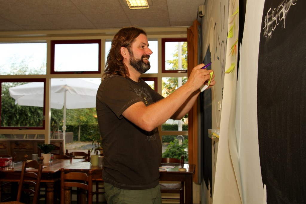 Johan Godschalk plakt tips op voor de ideeënbedenkers. Foto: Liesbeth Spaansen  © Achterhoek Nieuws b.v.