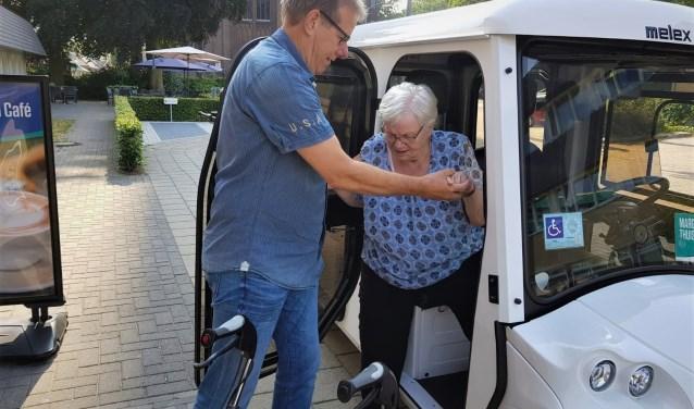 Vrijwilliger Jan Bongaarts helpt mevrouw Poelhuis uit de electrocar.