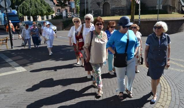 De Joodse gasten wandelen door het zonnige Aalten naar de Stolpersteine. Foto: Karin Stronks