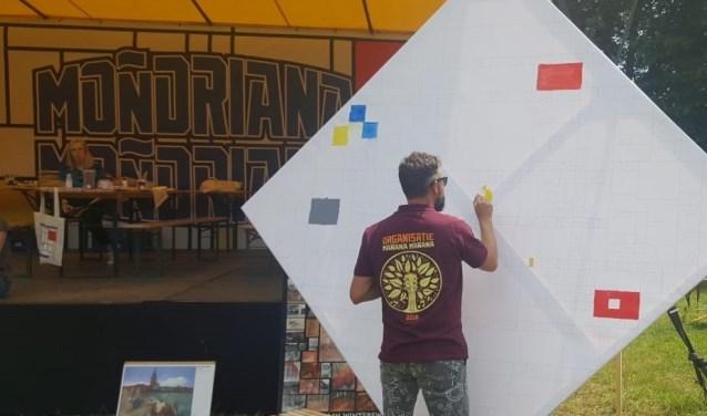 Festivaldirecteur Gijs Jolink schildert aan de Victory Boogie Woogie. Foto: PR