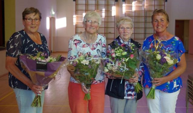 Diny Klompenhouwer, in de bloemetjes gezet vanwege haar grote verdiensten voor de zangvereniging, met naast  de jubilarissen Willey Weenink en Sien Beernink, dirigente Riet Lieverdink (vlnr). Foto: G. W. Huinink