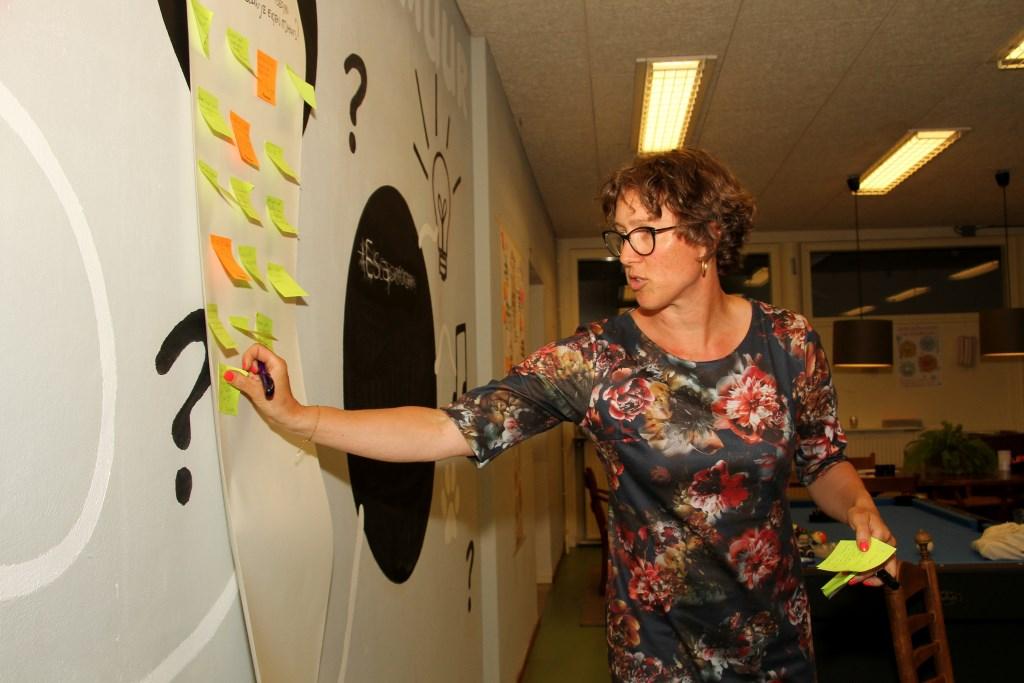 Linda Commandeur plakt tips op voor de ideeënbedenkers. Foto: Liesbeth Spaansen  © Achterhoek Nieuws b.v.