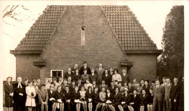 De belijdeniscatechisanten uit 1966 voor de voormalige pastorie aan de Domineesteeg met onder meer dominee Barnard .Foto: PR.