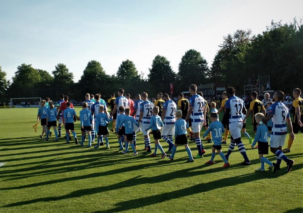 Aan de hand van de 'grote jongens' komen de spelers van HMC (Harreveld/Mariënvelde Combinatie) het veld op. Foto: Henri Walterbos  © Achterhoek Nieuws b.v.