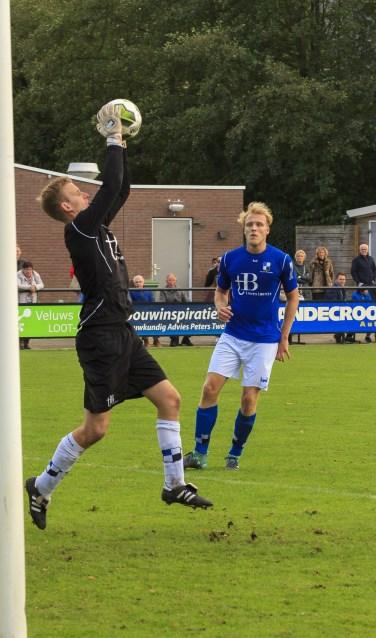 Lucas Breukelaar kijkt toe hoe Varsseveld-doelman Joost Riewald de bal uit de lucht plukt.  Foto: Henk Kok/Voorwaarts Twello