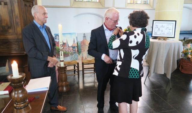 De scheidende dominee Wim Blanken krijgt het Draaginsigne opgespeld door echtgenote Dieneke. Foto: Theo Huijskes Foto:  © Achterhoek Nieuws b.v.