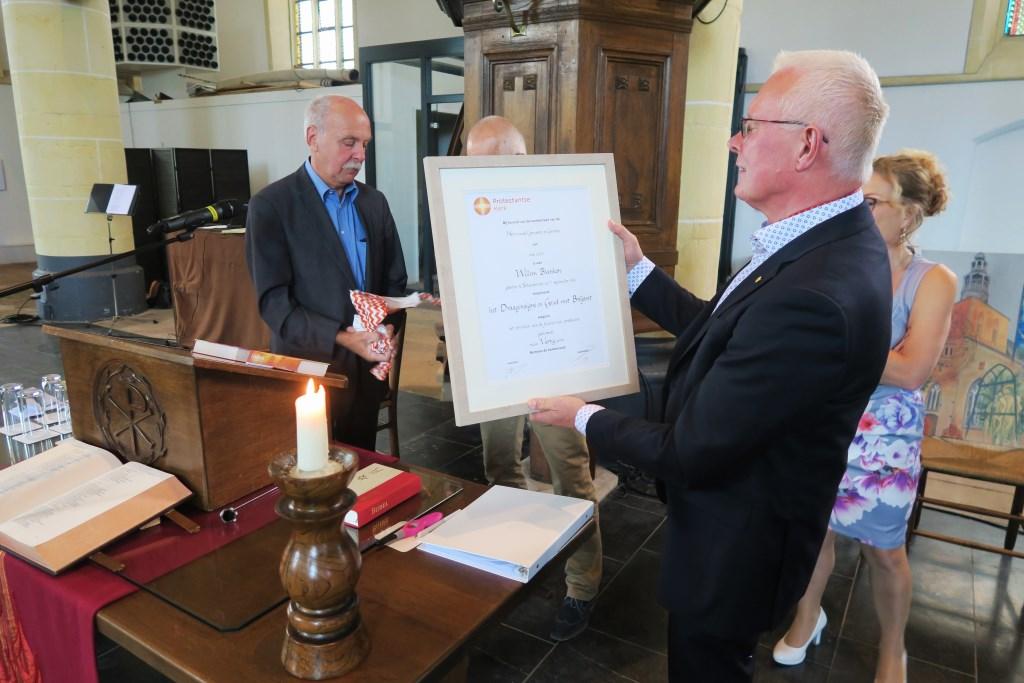 Dominee Wim Blanken bekijkt de oorkonde, behorende bij het door hem ontvangen Draaginsigne in Goud met Briljant. Foto: Theo Huijskes