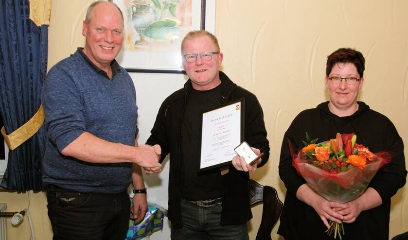 Harm Takke feliciteert Erik Messink met zijn jubileum. Rechts Jannet Messink.  Foto: Frank Vinkenvleugel