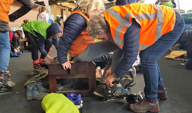 Martje Eggens helpt bij het aantrekken van de schaatsen. Foto: Alice Rouwhorst