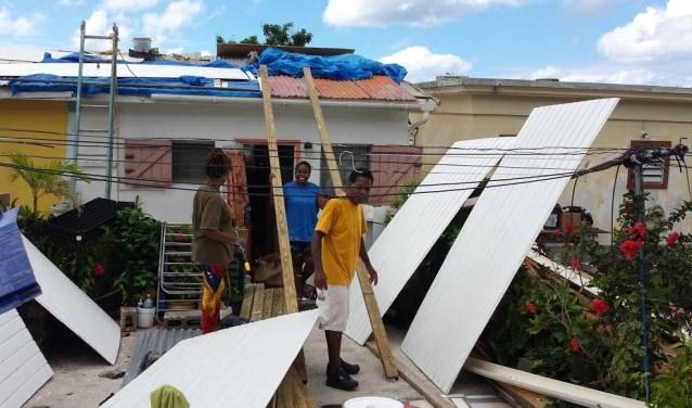 De familie Walsh bezig met het schilderen van het dakbeschot. Foto: eigen foto