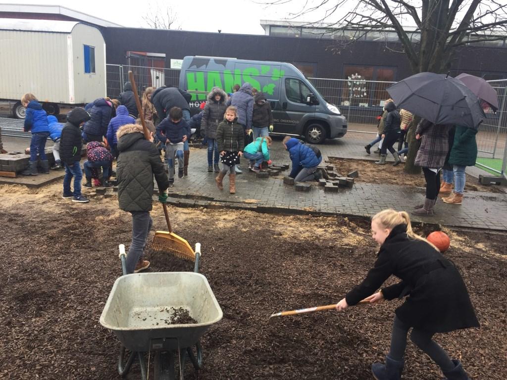Kruiwagens worden gevuld met houtsnippers. Foto: PR  © Achterhoek Nieuws b.v.