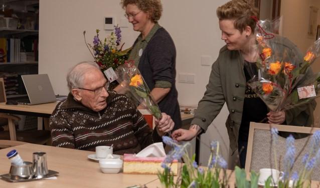 Debby van Aken geeft de heer W. Boeijink een roos. Op de achtergrond Ceciel Tankink. Foto: Rob Wanrooij