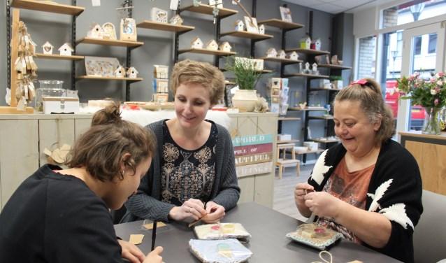 Zamani, Marianne (begeleider 's Heeren Loo) en Pascal pakken de zelfgemaakte producten in voor de verkoop. Foto: PR