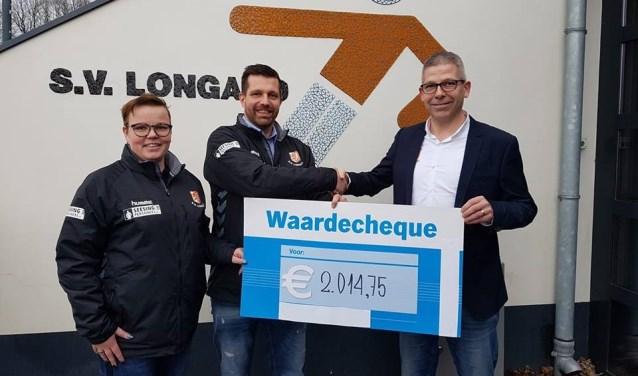 Olga Doppen en Roy van Melis overhandigen de cheque aan jeugdvoorzitter Roy Baks. Foto: PR