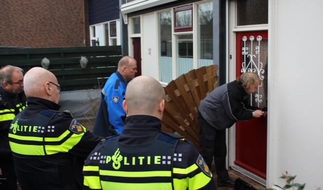 Sloten worden vervangen door de slotenmaker onder toeziend oog van de politie.Foto: Marlous Velthausz
