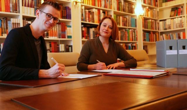 Wethouder Mathijs ten Broeke en uitgever Winnie Urban ondertekenen overdracht archief WalburgPers naar RAZ. Foto: PR