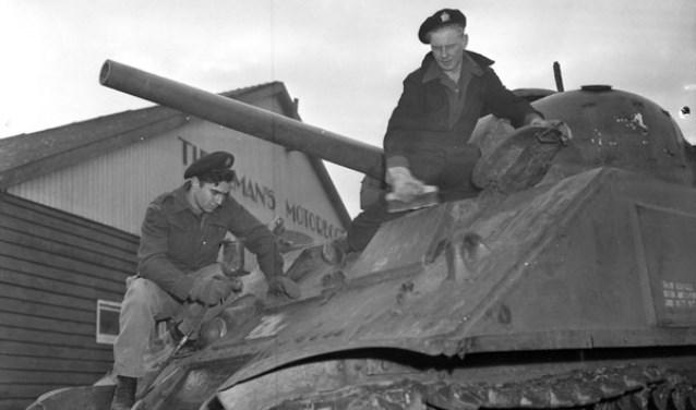 Soldaten poetsen de Sherman M4A4 tank, voor de werkplaats van Tieleman op 22 november 1945. Deze tank staat nu aan de Torontostraat in Doetinchem (Foto: Collectionscanada)