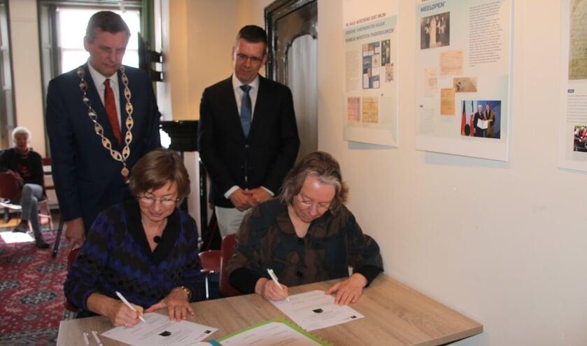 De ondertekening van de overdracht door Gerda Brethouwer en Claire Vaessen (rechts). Burgemeester Anton Stapelkamp en loco-burgemeester Joost Reus (staand rechts) kijken toe. Foto: Lydia ter Welle