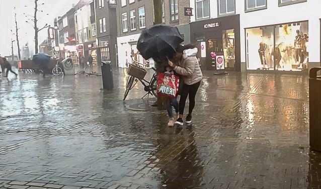 Deze dames trotseerden de regen en windstoten, gebult onder de paraplu die enkele ogenblikken later toch zou omklappen. Foto: Burry van den Brink