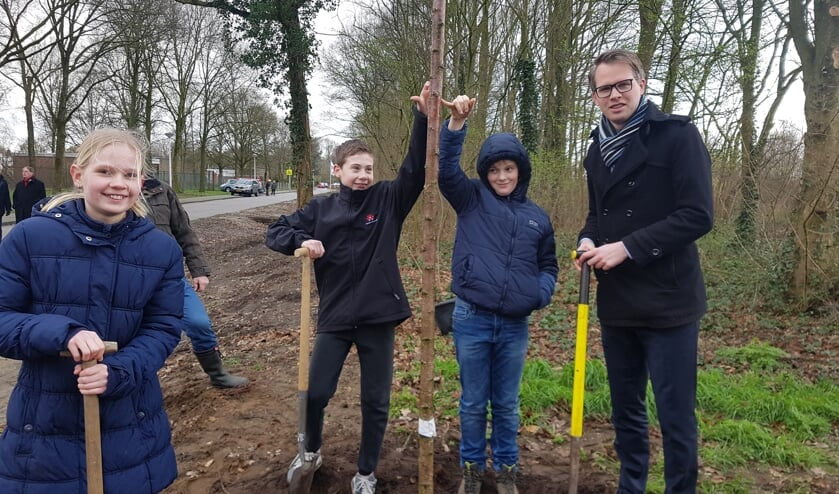 Wethouder Bart Porskamp plant, samen met vlnr. Sara, Niek en Krijn, een kersenboom. Foto: Kyra Broshuis