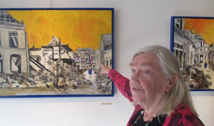 Ans van As-Berendsen voor een van haar schilderijen, wijzend naar haar ouderlijk huis in de Boliestraat. Foto: PR