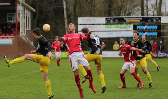 Rik van der Eerden probeert de bal te controleren, terwijl Jordi Lemmens van Staphorst hem daarbij hindert. Joost Rasing zit op de achtergrond in de houdgreep van Ewald Koster. Foto: Cor Hinkamp