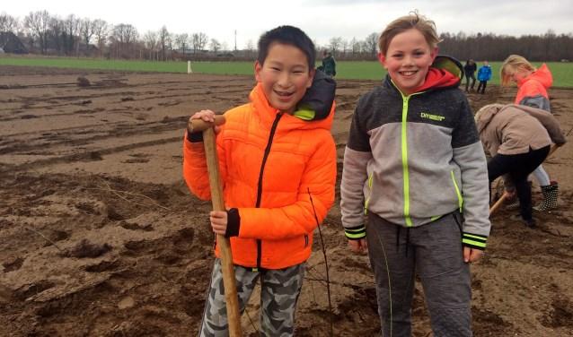 Jing en Finn plantten honderd struiken aan de Krommedijk in Hengelo tijdens Boomfeestdag. Foto:Diny Vink  © Achterhoek Nieuws b.v.