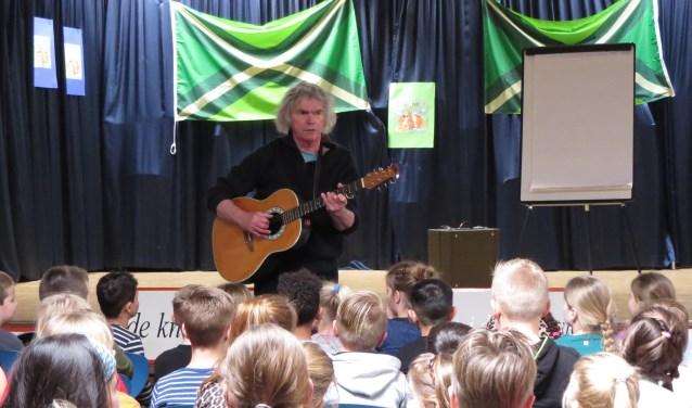 Hans Keuper weet kinderen van basisschool Op Koers te boeien met liedjes in het dialect. Foto: Josée Gruwel