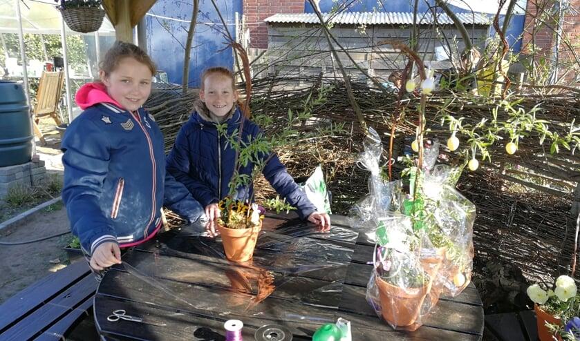 De leerlingen Zuzanna (l) en Britt maken de bloemstukjes voor de wijk klaar. Foto: Rob Weeber