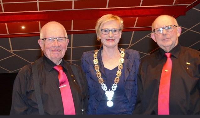 Jubilarissen van Harmonie Prinses Juliana Gert Klein Wentink (l .) en Johan Roenhorst (r.) werden gehuldigd door burgemeester Besselink. Foto: Arno Wolsink