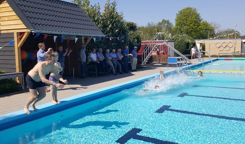 Rogier Vroeg in de Wei en zoon Rubèn duiken het pas geopende zwembad in, toegekeken door publiek in De Hut dat vrijdagmiddag eveneens werd geopend. Foto: Marjan Lijftogt